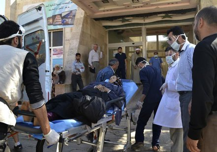 A woman affected by what activists say was a gas attack on the town of Telminnes is transferred to Bab al-Hawa hospital, which is close to t