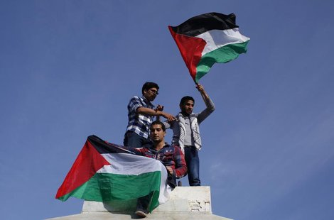 Palestinians hold national flags as they celebrate after an announcement of a reconciliation agreement in Gaza City April 23, 2014. REUTERS/