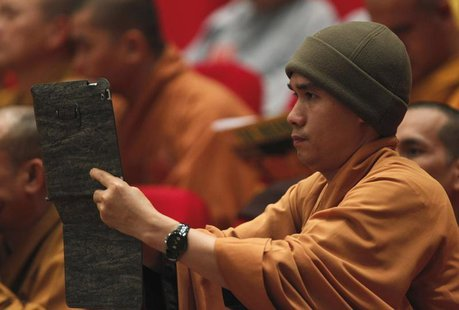 A Buddhist monk films, with an iPad, the closing ceremony of the seventh congress of Vietnam's Buddhist Sangha Association in Hanoi November