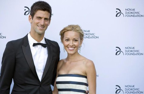 Serbian tennis player Novak Djokovic and his girlfriend Jelena Ristic pose for photographers as they arrive at a fundraising dinner for the