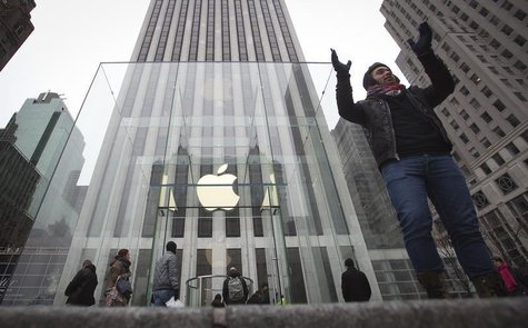 A man poses for a photo in front of the Apple store on 5th Avenue in New York, December 26, 2013. REUTERS/Carlo Allegri