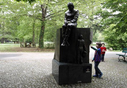 Children play next to the memorial statue of Formula One Brazilian driver Ayrton Senna in the park inside the race track at Imola April 22,