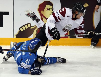 Latvia's Ralfs Freibergs (top) trips over Finland's Antti Pihlstrom during their 2013 IIHF Ice Hockey World Championship preliminary round m