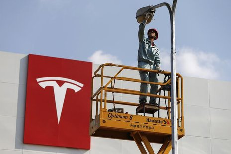 A labourer repairs a street lamp next to a logo of Tesla Motors in front of a new showroom of the company in Shanghai, April 22, 2014. REUTE