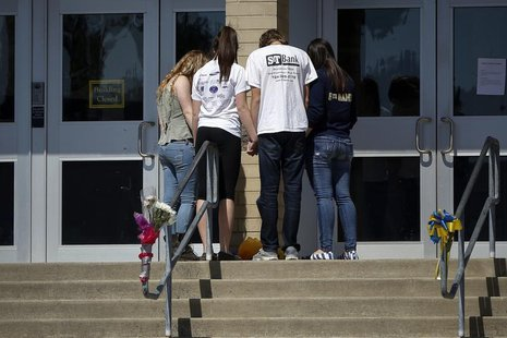 Students hold hands outside the entrance to Franklin Regional High School in Murrysville, Pennsylvania April 10, 2014. REUTERS/Shannon Stapl