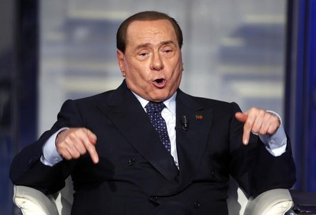 Italy's former Prime Minister Silvio Berlusconi gestures as he appears as a guest on the RAI television show Porta a Porta (Door to Door) in