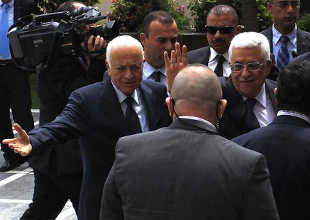 Arab League Chief Nabil al-Arabi (L) greets Palestinian President Mahmoud Abbas, who waves to the media, before attending an Arab Foreign Mi