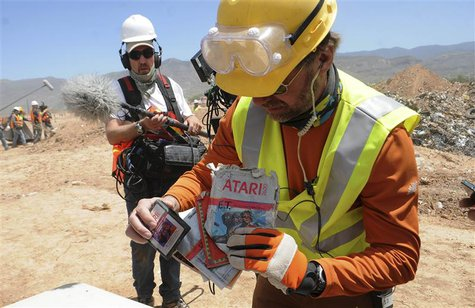 Archaeologist Andrew Reinhard (R) shows off the first E.T. the Extra-Terrestrial cartridges recovered from the old Alamogordo landfill, in A