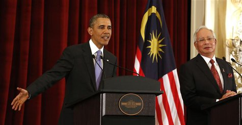 U.S. President Barack Obama talks next to Malaysian Prime Minister Najib Razak as they both participate in a news press conference at the Pe