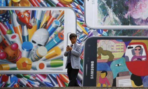 A man uses his mobile phone in front of a giant advertisement promoting Samsung Electronics' new Galaxy S5 smartphone, at an art hall in cen