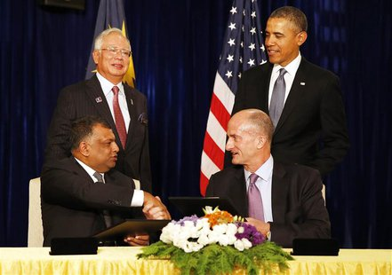U.S. President Barack Obama (standing R) and Malaysian Prime Minister Najib Razak (standing L) witness the signing of a major business agree