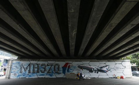 A man walks past graffiti of the missing Malaysia Airlines Flight MH370 in Kuala Lumpur April 15, 2014. REUTERS/Samsul Said