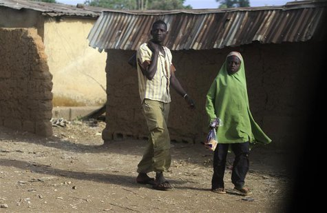 A man and a girl walk on a street in Bakin Kogi, Zango kataf, Kaduna State, March 22, 2014. Picture taken March 22, 2014. REUTERS/Afolabi So