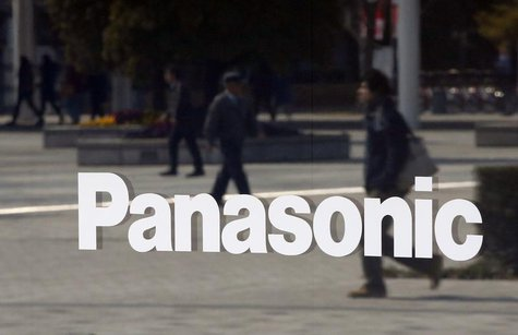 People walking past are reflected in a sign at Panasonic Center Tokyo in Tokyo March 12, 2014. REUTERS/Toru Hanai