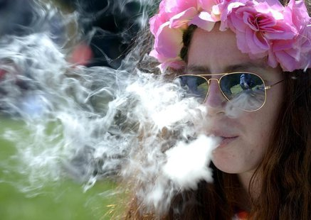 A woman smokes marijuana during the 4/20 Rally at the Civic Center in Denver, Colorado, April 20, 2014. REUTERS/Mark Leffingwell