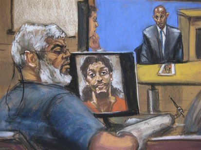 Abu Hamza al-Masri, the radical Islamist cleric facing U.S. terrorism charges, sits while a picture of shoe bomber Richard Reid is seen on a