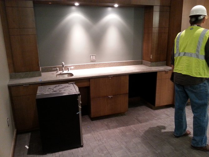 A reverse angle of an unfinished suite. Here you can see the counter with sink and refrigerator.