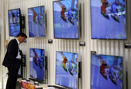 A customer looks at LG Electronics' TV sets which are made with LG Display flat screens at its store in Seoul January 23, 2014. REUTERS/Kim