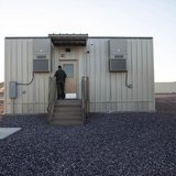 A border patrol agent opens the entrance to a temporary holding facility at the U.S. Department of Homeland Security's Forward Operating Bas