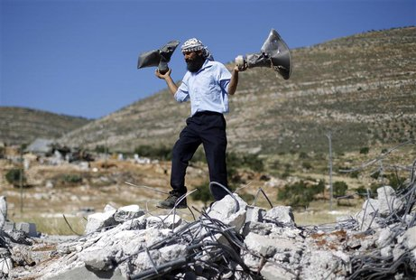 A Palestinian man holds damaged loudspeakers belonging to a mosque after it was demolished by Israeli bulldozers in Khirbet Al-Taweel villag