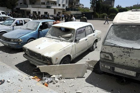 Damaged vehicles are seen after mortar bombs landed on two areas in Damascus April 29, 2014, in this handout photograph released by Syria's