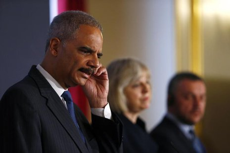 (From L to R) U.S. Attorney General Eric Holder scratches his ear as he answers a question during a news conference with Britain's Home Secr