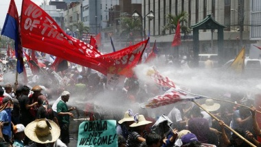 Protesters are sprayed with water cannons outside the U.S. Embassy in Manila in protest to the visit by President Obama.  REUTERS/Erik De Castro