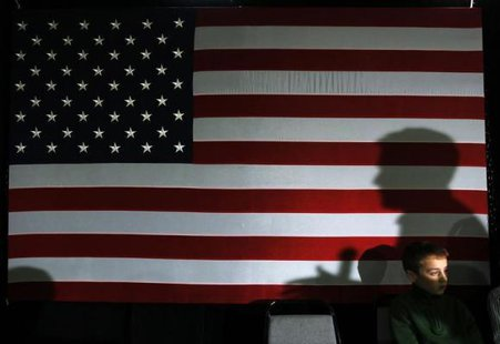 Republican presidential candidate and former Massachusetts Governor Mitt Romney casts a shadow on a U.S. flag while speaking at a ''We the People Freedom Forum'' in Hudson, New Hampshire December 11, 2011. CREDIT: REUTERS/BRIAN SNYDER
