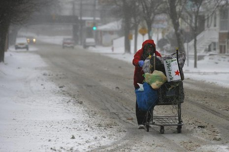 A man pushes a cart up the road while scavenging for bottles and cans during a winter nor'easter snowstorm in Lynn, Massachusetts January 2,