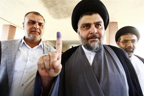 Shiite cleric Moqtada al-Sadr shows his ink-stained finger at a polling station during parliamentary election in Najaf, south of Baghdad Apr