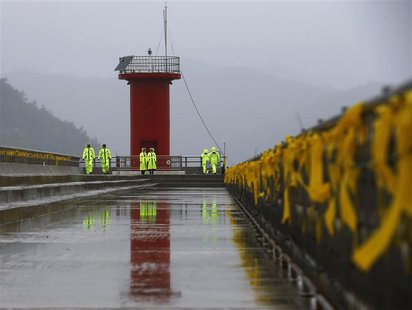 Police officers stand guard at a pier, as yellow ribbons dedicated to missing and dead passengers on board the capsized Sewol ferry are tied
