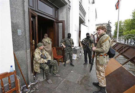 Pro-Russian armed men gather at the entrance to the regional government headquarters in Luhansk, eastern Ukraine, April 30, 2014. REUTERS/Va