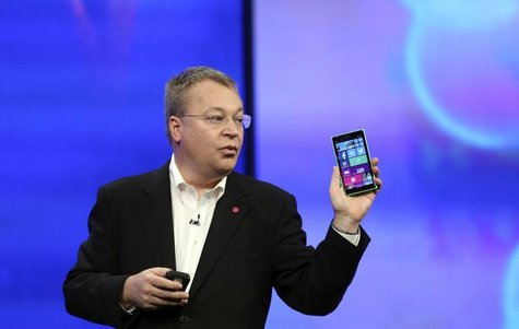 "Stephen Elop, vice president of Nokia, gestures while introducing the Nokia Lumia 930 mobile phone during Microsoft's ""build"" conference in"