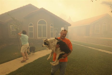 People evacuate from their homes as a wildfire driven by fierce Santa Ana winds closes in on them in Rancho Cucamonga, California, April 30,