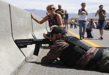 Protester Eric Parker from central Idaho aims his weapon from a bridge next to the Bureau of Land Management's base camp where seized cattle