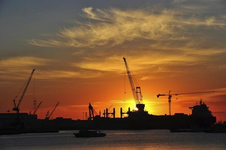 A shipyard is silhouetted against the rising sun in Dalian, Liaoning province, Janaury 28, 2014. REUTERS/China Daily