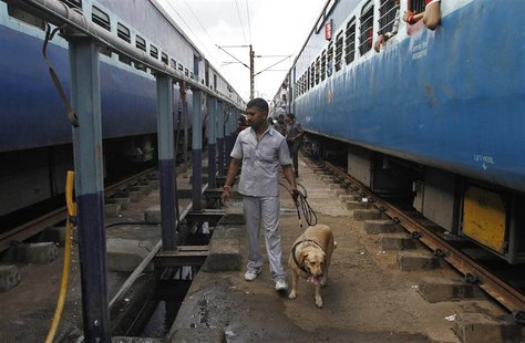 A member of a bomb disposal squad with a sniffer dog examines a passenger train (L) in which two explosions occurred, at the railway station