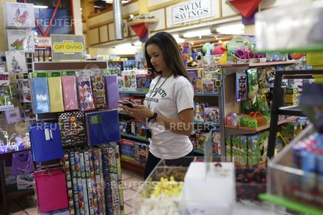 Store employee Ashley Beal takes an order via a smartphone app to be delivered to the customer by a Google car and courier at a toy and spor