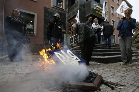 Pro-Russia activists burn Ukranian coat of arms outside the prosecutor's office in Donetsk May 1, 2014. REUTERS/Marko Djurica