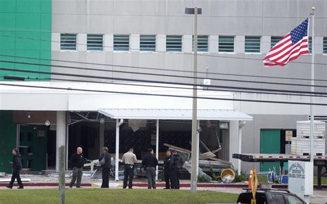 Police officers maintain a cordon after an apparent gas explosion killed two and injured over 100 inmates and guards at Escambia County jail