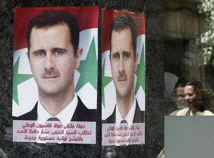 "Posters of Syrian President Bashar al-Assad placed by pro-Assad group ""Qasion Forum"", calling for him to run for a third term, are seen at a"
