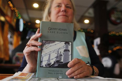 Peggy Kelly, owner of Murphy's Law pub, poses for a photograph with a book by Sinn Fein leader Gerry Adams in the South Boston neighborhood