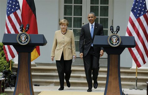 U.S. President Barack Obama and German Chancellor Angela Merkel arrive for a joint news conference in the Rose Garden of the White House in
