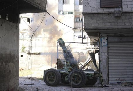 Rebel fighters fire an artillery cannon towards forces loyal to Syria's President Bashar al-Assad in eastern al-Ghouta, near Damascus April