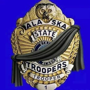 An illustration showing a black band across an officer's shield appears on the official Facebook page of the Alaska State Troopers in Anchor