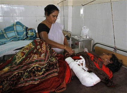 A member of medical staff tends to Phuleja Khatun, 25, who was injured in an attack, inside a hospital in the northeastern Indian city of Gu