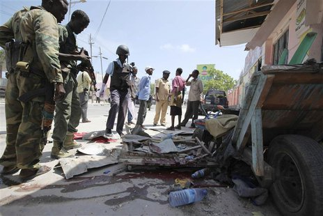 Somali soldiers stand at the scene of an explosion in the capital Mogadishu May 3, 2014. At least three people were killed and several wound