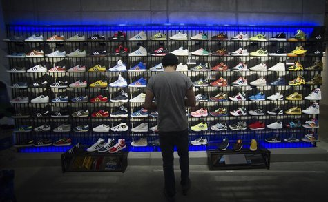 A man stands in front of a rack with Adidas Original shoes before the opening at the new Adidas Originals store in Berlin, March 27, 2014. R