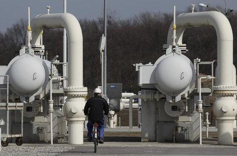 A worker rides a bicycle past gas pipes at Gas Connect Austria's gas distribution node in Baumgarten some 40 km (25 miles) east of Vienna Ma
