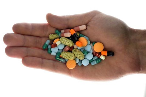 A person holds pharmaceutical tablets and capsules in this picture illustration taken in Ljubljana September 18, 2013. Picture taken Septemb